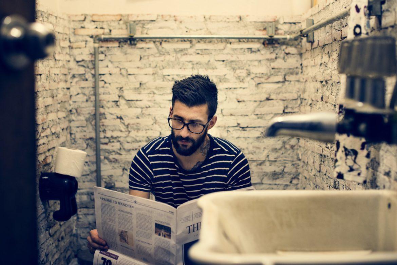 Man in a restroom reading newspaper
