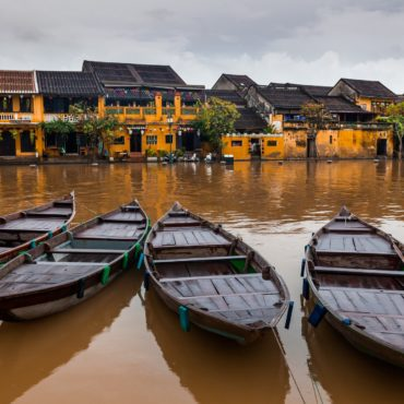 Traditional boats in front of ancient architecture in Hoi An, Vietnam.