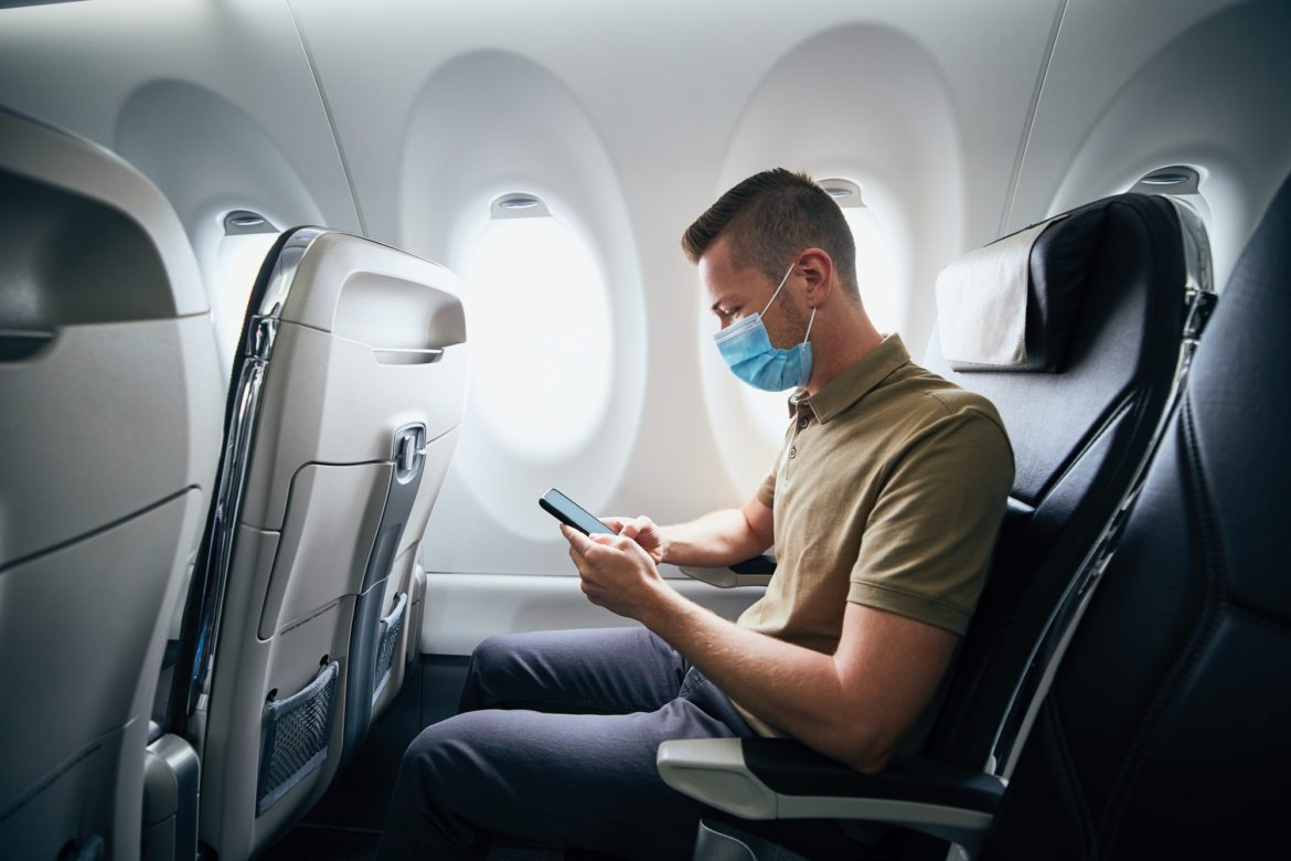 Man wearing face mask inside airplane