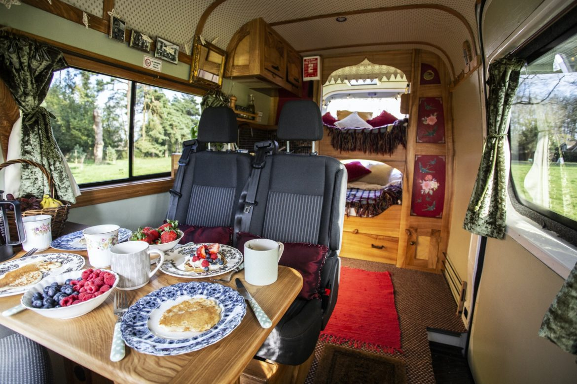 Interior view of camper van with breakfast on table.