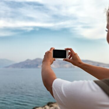 Hiker girl with smartphone taking landscape photo of sea bay while traveling