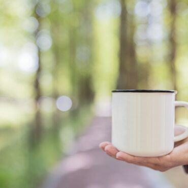 Woman hand holding metallic coffee mug in forest at early morning. Mockup with copy space