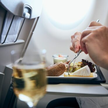 Airline meal and beverage served on seat tables during flight.